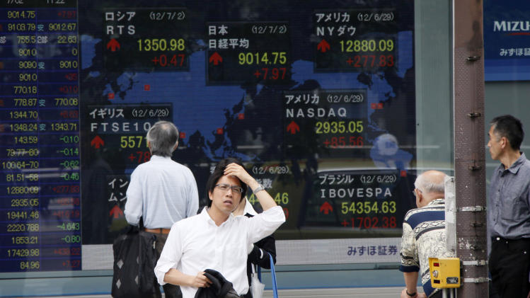 A man waits to cross a road as others watch a digital display of global stock indexes outside a securities firm in Tokyo Monday, July 2, 2012. Asian stock markets inched higher Monday amid continued optimism over Europe's moves to ease its debt crisis and economic malaise. (AP Photo/Koji Sasahara)