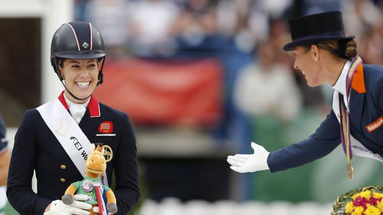 British rider Dujardin jokes with Cornelissen of Netherlands after winning the gold medal at the Individual freestyle Competition Dressage event at the World Equestrian Games at the d'Ornano stadium in Caen