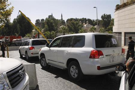 U.N. vehicles transporting a team of OPCW experts, leave their hotel in Damascus