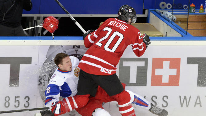 Russia's Yaroslav Dyblenko (28) is checked against the boards by Canada's Brett Ritchie (20) during the first period of the bronze medal hockey game at the IIHF World Junior Championships, Saturday, Jan. 5, 2013, in Ufa, Russia. (AP Photo/The Canadian Press, Nathan Denette)