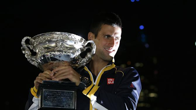 Serbia's Novak Djokovic poses for photographers as he holds his trophy aloft after defeating Britain's Andy Murray in the men's final at the Australian Open tennis championship in Melbourne, Australia, Monday, Jan. 28, 2013.  (AP Photo/Aaron Favila)