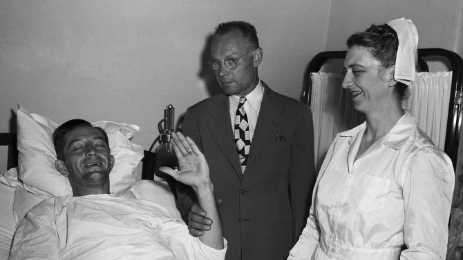 "FILE - In this June 17, 1949 file photo, Philadelphia Phillies first baseman Eddie Waitkus smiles from his bed in Illinois Masonic Hospital in Chicago as his father, Stephen, holds up his arm for an attempted wave. Waitkus was shot and seriously wounded June 14 in a Chicago hotel by 19-year-old Ruth Steinhagen. Steinhagen died of natural causes at 83 in late December 2012. Her death is the final chapter in one of the most sensational and bizarre criminal cases in Chicago history that made headlines around the country. She was the inspiration for Bernard Malamud's novel ""The Natural"" and the 1984 movie starring Robert Redford. (AP Photo/File)"