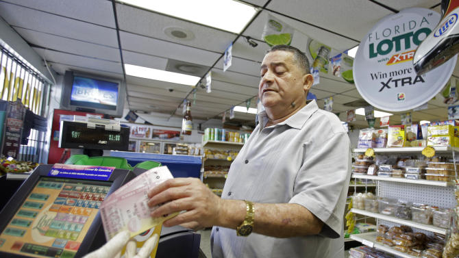 Remberto Gonzalez purchases Powerball lottery tickets at a local store in Hialeah, Fla., Tuesday, Aug. 6, 2013. On Tuesday, the Powerball jackpot reached $425 million for Wednesday's drawing. (AP Photo/Alan Diaz)