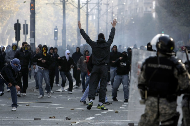 FILE - In this Sunday, Oct. 10, 2010 file photo, protesters throw stones at riot police protecting a gay pride march in Belgrade, Serbia. Serbia&#39;s police on Wednesday, Oct. 3, 2012, banned a gay pride march in Belgrade planned for the weekend, citing security concerns but also complying with a request from Serbia&#39;s Christian Orthodox church. (AP Photo/Marko Drobnjakovic, File)