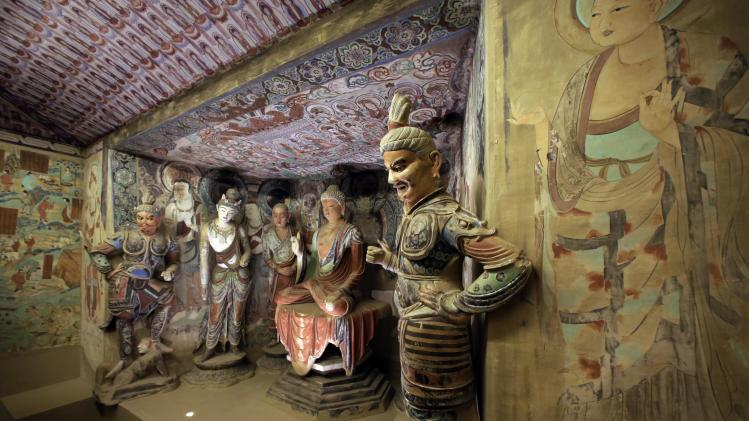 """A full scale replica cave from the 8th century that contains the Bodhisattva of the Mogao Caves is presented in """"Dunhuang: Buddhist Art at the Gateway of the Silk Road,"""" at the China Institute, in New York,  Tuesday, April 24, 2013. (AP Photo/Richard Drew)"""