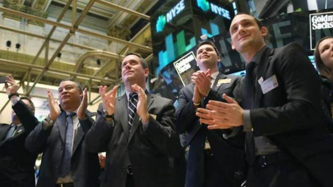 Visitors to the New York Stock Exchange applaud after the Dow Jones and the S&P both hit five-year highs on Jan. 24.