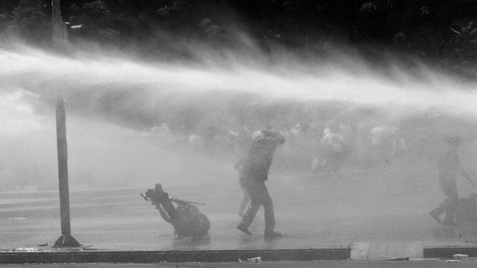A news cameraman, left, falls on the ground as Turkish riot police spray water cannon at demonstrators who remained defiant after authorities evicted activists from an Istanbul park, making clear they are taking a hardline against attempts to rekindle protests that have shaken the country, in city's main Kizilay Square in Ankara, Turkey, Sunday, June 16, 2013. (AP Photo/Burhan Ozbilici)