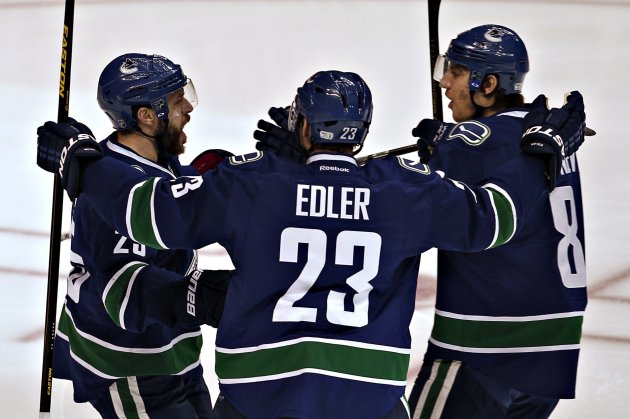Canucks' Ebbett celebrates his goal against Predators with Edler and Tanev during the first period of their NHL hockey game  in Vancouver