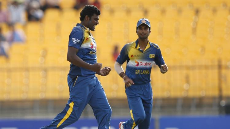 Sri Lanka's Perera celebrates with teammate Chandimal after taking the wicket of Pakistan's Akmal during their first ODI cricket match in Hambantota