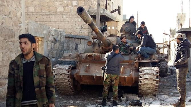 Government forces chat near a tank three kilometres from the Shiite villages of Nabbul and Zahra in Syria's northern Aleppo province on February 2, 2016