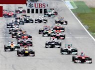 Spain's Ferrari driver Fernando Alonso, right, leads the field right after the start of the German F1 Grand Prix in Hockenheim, Germany,  Sunday, July 22, 2012. (AP Photo/Michael Probst)