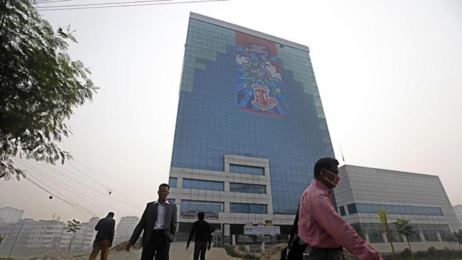 """In this Saturday, Dec. 8, 2012, photo, people walk outside the headquarters of the Bangladesh Garment Manufacturers and Export Association (BGMEA) in Dhaka, Bangladesh. About a year before a November fire at a clothing factory in Bangladesh killed 112 people, executives from Wal-Mart, Gap and other big clothing companies met nearby in the country's capital to discuss a legally binding contract that would govern safety inspections. But after a spokeswoman for Wal-Mart, the world's largest retailer, got up and said the proposal wasn't """"financially feasible,"""" the effort quickly lost momentum. (AP Photo/A.M. Ahad)"""