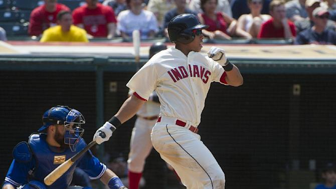 Cleveland Indians' Michael Brantley, right, watches his line drive single off Toronto Blue Jays' Jeff Francis as Blue Jays' catcher Russell Martin, left, looks on during the fifth inning of a baseball game in Cleveland, Sunday, May 3, 2015. The Indians won the game 10-7. (AP Photo/Phil Long)