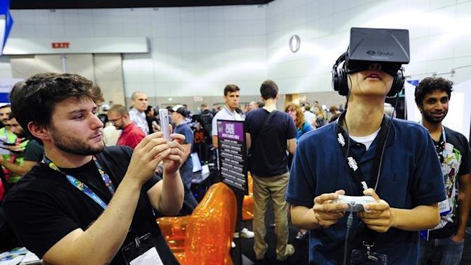 "Software designer Julian Kantor who created ""The Recital"" takes a picture of Jonathan Feng as he uses the Oculus Rift virtual reality headset to experience his program during E3 in Los Angeles"