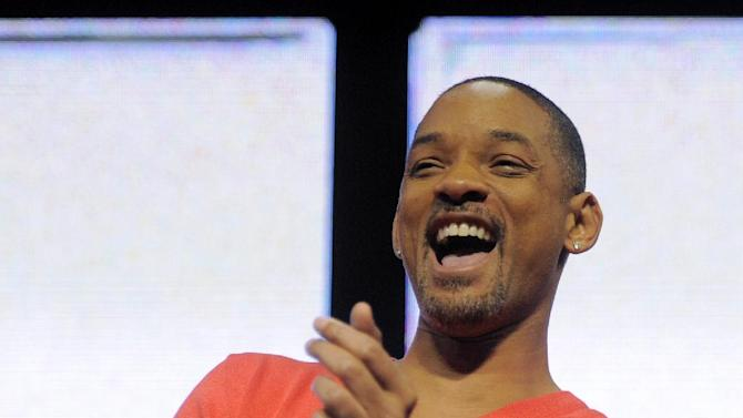 """FILE - In this Jan. 9, 2012 file photo, actor Will Smith laughs after viewing a """"Men in Black 3"""" movie trailer during a Sony news conference at the 2012 International CES in Las Vegas. Nickelodeon will kick off the 25th annual Kids' Choice Awards live Saturday night at 8 p.m. with host Will Smith. (AP Photo/Jack Dempsey, file)"""