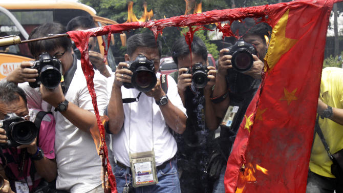 Photographers take pictures as former police officer Abner Afuang burns a Chinese flag in front of the Department of Foreign Affairs to oppose the presence of Chinese vessels in the disputed territory in the South China Sea Friday, July 27, 2012 in suburban Pasay City, south of Manila, Philippines. Afuang called on the government to persist on its claim on Scarborough Shoal which is within the country's economic zone. (AP Photo/Photo/Pat Roque)