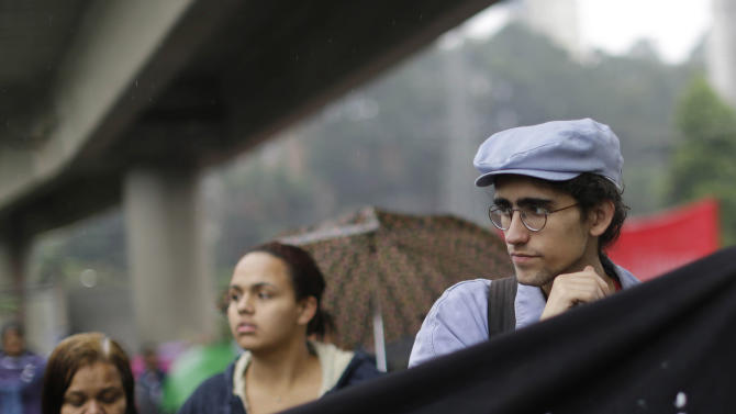 """Free Fare Movement member Caio Martins, right, participates in a protest at Capao Redondo neighborhood in Sao Paulo, Brazil, Tuesday, June 25, 2013. The """"horizontally"""" organized wing of mostly young university students have been calling for the elimination of bus and subway fares since 2003. """"Look, we're not the owners of these protests across Brazil nor are we the only group behind them,"""" said Martins, a 19-year-old university student who helped orchestrate Tuesday's protest. """"That said, we are one of the most organized groups involved in what's going on. I think that's why people have looked to us."""" (AP Photo/Nelson Antoine) (AP Photo/Nelson Antoine)"""