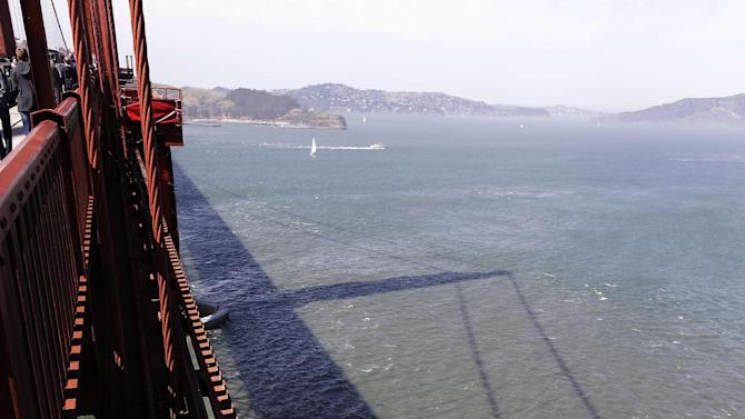 In the photo taken Tuesday, April 30, 2013 a shadow of the Golden Gate Bridge is cast onto San Francisco Bay in San Francisco. About 1,500 people have plunged from the bridge, making it one of the world's favorite suicide spots. (AP Photo/Eric Risberg)