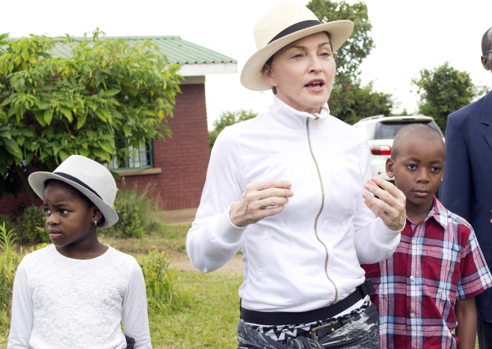 US performer Madonna, centre, tours the Mphandura orpahange near Lilongwe, Malawi, Friday April 5, 2013.  Madonna, is spending her fourth day in the southern African country from where she adopted two children David Banda, right and Mercy James, left. (AP Photo/Thoko Chikondi)