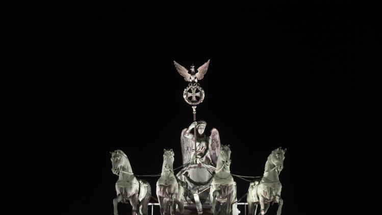 The illuminated Quadriga at top of the Brandenburger Gate is seen prior to Earth Hour in Berlin, Saturday, March 23, 2013. Earth Hour was marked worldwide at 8.30 p.m. local time and is a global call to turn off lights for 60 minutes in a bid to highlight the global climate change.(AP Photo/Markus Schreiber)