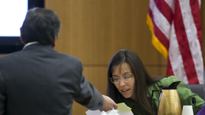 Prosecutor Juan Martinez hands evidence to show Jodi Arias during cross examination during the Jodi Arias trial at Maricopa County Superior Court in Phoenix on Wednesday, Feb. 27, 2013. Arias is charged in the June 2008 death of her lover in his suburban Phoenix home. She says it was self-defense, but police say she planned the attack on Travis Alexander in a jealous rage.  (AP Photo/The Arizona Republic, David Wallace, Pool)