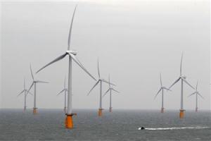 A boat powers past the Thanet Offshore Wind Farm off the Kent coast in southern England