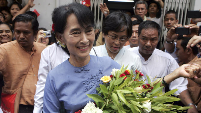 Myanmar opposition leader Aung San Suu Kyi, center, is greeted by supporters as she arrives to attend the opening ceremony of a branch office of her National League for Democracy (NLD) party on Tuesday, May 8, 2012, in Yangon, Myanmar. (AP Photo/Khin Maung Win)