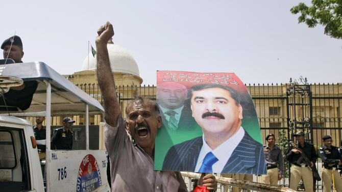 A supporter of Pakistan's ruling People's party reacts while holding a poster showing Prime Minister Yousuf Raza Gilani, during a protest to condemn the verdict against Gilani, in Karachi, Pakistan, Thursday, April 26, 2012. Pakistan's Supreme Court convicted the prime minister of contempt on Thursday but gave him only a symbolic few minutes of detention inside the court, leaving the premier in power but weakened and facing fresh calls to resign, a punishment that could be used as the basis to push Gilani from power in the months to come. (AP Photo/Fareed Khan)