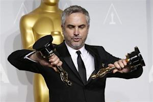 """Alfonso Cuaron poses with the awards for best director and best film editing for """"Gravity"""" at the 86th Academy Awards in Hollywood"""
