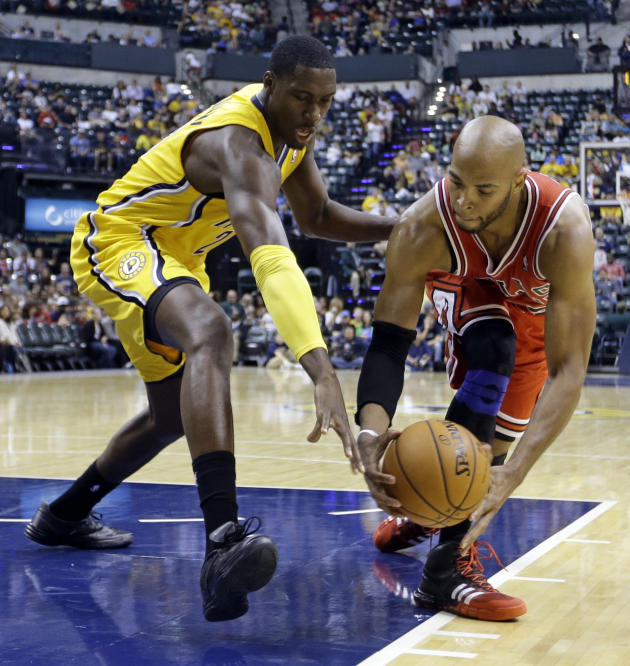 Indiana Pacers center Roy Hibbert, left, attempts to knock the ball away from Chicago Bulls forward Taj Gibson in the first half of an NBA preseason basketball game in Indianapolis, Saturday, Oct. 5,