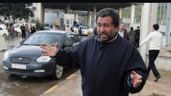 An injured man seen at the Cilvegozu customs gate on the Turkey-Syria border near Reyhanli, Hatay, Turkey, Monday, Feb. 11, 2013,  minutes after a car bomb exploded. Turkey's Deputy Drime Minister Bulent Arinc said 12 people died and 28 were wounded and taken to hospitals in Turkey. (AP Photo/Gaia Anderson)