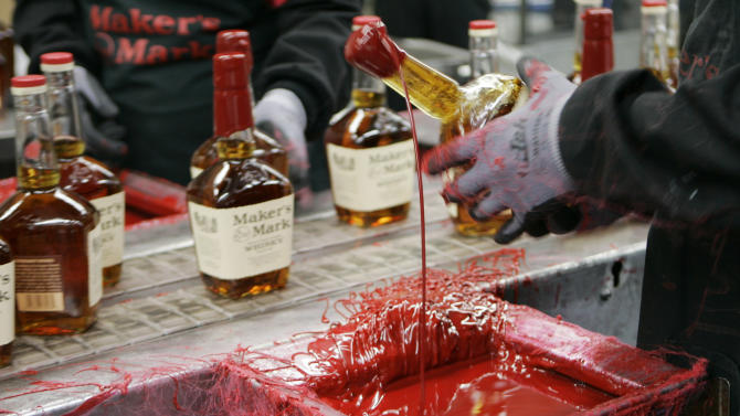 FILE - In this Wednesday, April 8, 2009, file photo, a bottle of Maker's Mark bourbon is dipped in red wax during a tour of the distillery in Loretto, Ky. Kentucky bourbon makers have stashed away their largest stockpiles in more than a generation due to resurgent demand for the venerable brown spirit. (AP Photo/Ed Reinke, File)