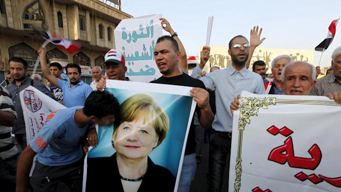 An Iraqi protester kisses a picture of German Chancellor Angela Merkel during demonstration against the poor quality of basic services, power outages and calling for trial of corrupt politicians in Baghdad