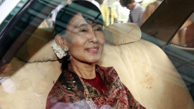 Myanmar opposition leader Aung San Suu Kyi sits in a car after arriving at Yangon International Airport in Yangon, Myanmar, Sunday, June 3 2012 after returning from Thailand. Suu Kyi completed her first trip out of Myanmar in 24 years on Sunday, a tour that highlighted her new freedom to explore the world - and to return home. (AP Photo/Khin Maung Win)