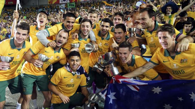 Australia's players pose for pictures with their trophies and the Asian Cup after they beat South Korea to win the tournament at the Stadium Australia in Sydney