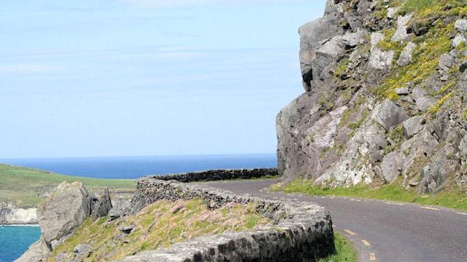 This May 29, 2012, photo shows the swerving road at the tip of the Dingle Peninsula in County Kerry, Ireland. Ireland is about 300 miles from north to south and a driving trip in the country's western region takes you along hilly, narrow roads with spectacular views ranging from seaside cliffs to verdant farmland.  (AP Photo/Jake Coyle)