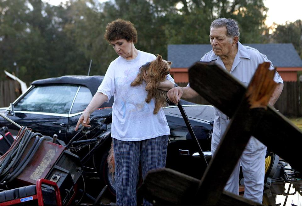 Diane, 69, and Raymond Pierce, 72, survey damage to their property after strong winds from a suspected tornado passed through the Lafayette Woods subdivision Wednesday, Nov. 16, 2011  in Houma, La. No one was injured. (AP Photo/The Houma Courier, Julia Rendleman)