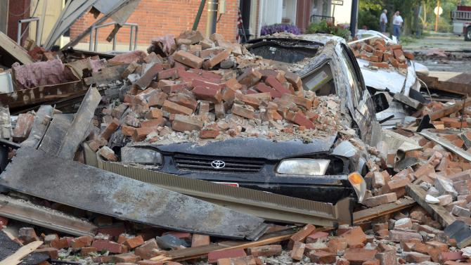 In this Friday, June 29, 2012 photo, a car sits damaged from where a brick wall fell on it from the second story of a store in Columbus Grove, Ohio. The bricks fell on and crushed two vehicles as strong winds tore through the region Friday afternoon. (AP Photo/The Lima News, Jay Sowers)