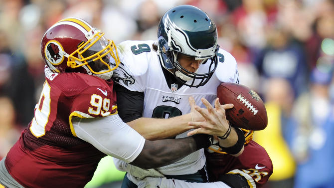 Philadelphia Eagles quarterback Nick Foles is sacked by Washington Redskins defensive end Jarvis Jenkins, left, and cornerback Josh Wilson, right, during the first half of an NFL football game in Landover, Md., Sunday, Nov. 18, 2012. (AP Photo/Nick Wass)