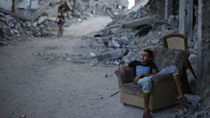 A Palestinian boy sits on a couch outside his house, which witnesses said was destroyed during the Israeli offensive, in Gaza City