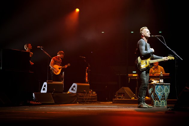 Sting fronting his band on stage at the Indoor Stadium. His band included a lead guitarist, a drummer, a keyboardist, a backup vocalist and a mandolin/violin player. (Photo courtesy of Sony Pictures)