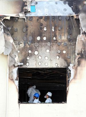 Police officers investigate in a burned out hospital in Jangseong, South Korea, Wednesday, May 28, 2014. A fire at the hospital annex housing elderly patients in the southwestern county of Jangseong killed 21 people early Wednesday, officials said. (AP Photo/Yonhap, Hyung Min-woo) KOREA OUT
