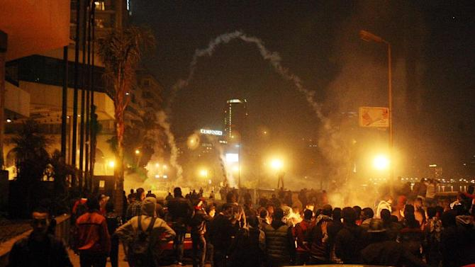 In this Saturday, Jan. 26, 2013 photo, demonstrators throw stones at security forces who respond with tear gas in front of international hotels along the Nile in downtown Cairo, Egypt. Unrest surrounding the second anniversary of Egypt's revolution broke out in Cairo and other cities for a third day, with protesters clashing for hours with riot police who fired tear gas that encompassed swaths of the capital's downtown. (AP Photo/Mohammed Abu Zaid)