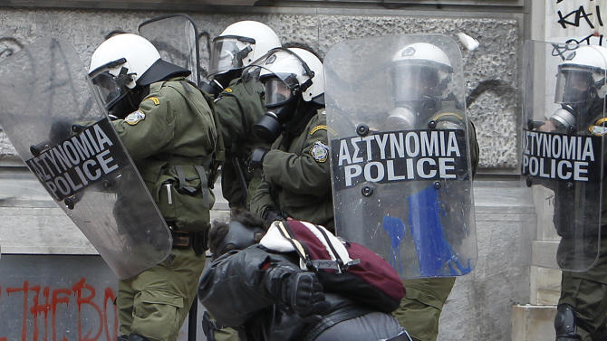 A protester in foreground throws a stone at riot police during clashes in Athens, Friday, Feb. 10, 2012.  Thousands took to the streets of Athens as unions launched a two-day general strike against planned austerity measures on Friday, a day after Greece's crucial international bailout was put in limbo by its partners in the 17-nation eurozone. (AP Photo/Thanassis Stavrakis)