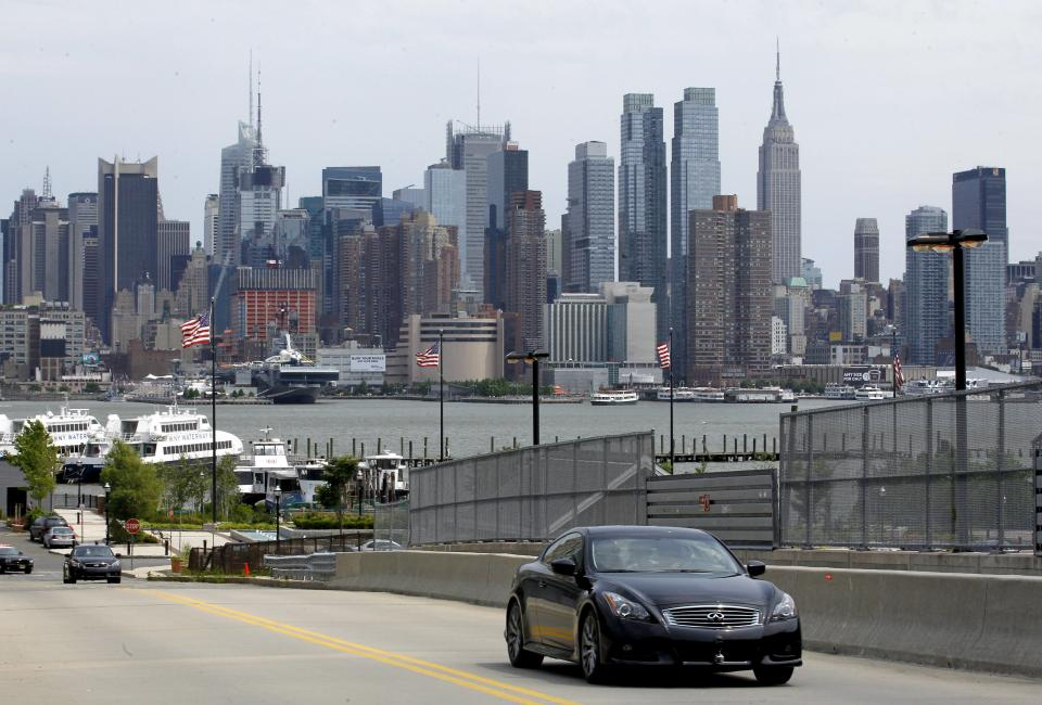 With the New York City skyline as a background, a vehicle driven by defending Formula One champion Sebastian Vettel climbs a hill, Monday, June 11, 2012, in Weehawken, N.J. Vettel drove a 3.2-mile course to demonstrate the planned route for next year's Grand Prix of America race. (AP Photo/Julio Cortez)