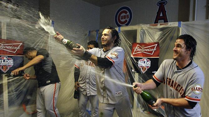 San Francisco Giants' Brandon Crawford, center, and Ryan Theriot, right, spray champagne in the locker room after they defeated the Cincinnati Reds 6-4 in Game 5 of the National League division baseball series, Thursday, Oct. 11, 2012, in Cincinnati.  The Giants won the final three games, all in Cincinnati, and advanced to the NL championship series. (AP Photo/David Kohl)