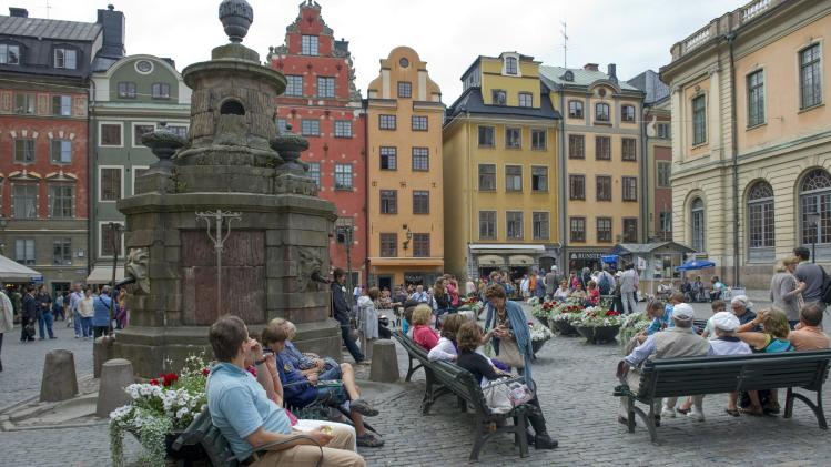This is a July 26, 2011 file photo of tourists in Stortorget Square in the Old Town of Stockholm. Buildings from the 17th century stand askew, worn by time but meticulously repaired and repainted in soft shades of yellow and rose. Unless you're looking for a plastic Viking helmet, turn off the main street and its gift shops and discover a plethora of small boutiques, art galleries and fashionable cafes. (AP Photo/Leif R Jansson, File) SWEDEN OUT