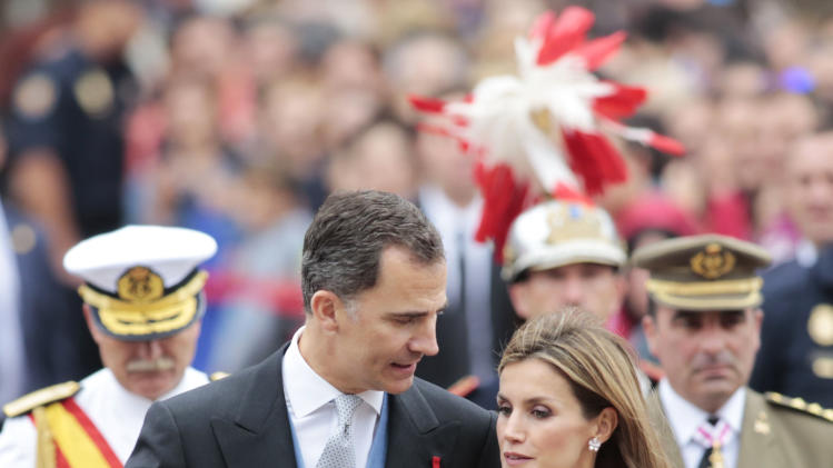 Spain's King Felipe VI and Queen Letizia walk along the Obradoiro square during celebrations for St James' Day in Santiago de Compostela