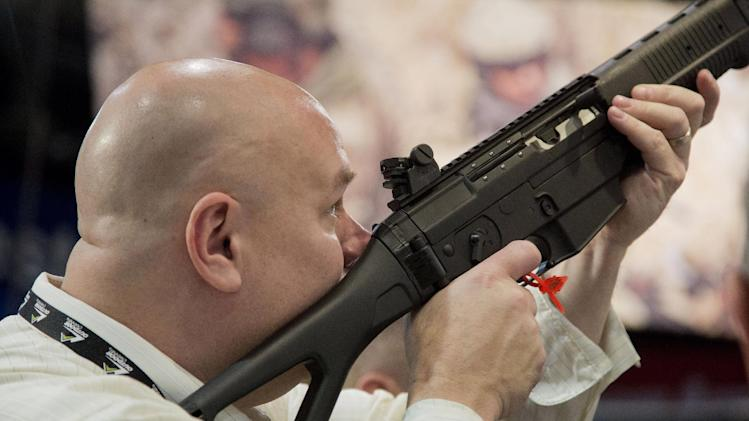 A convention attendee looks through the sight of a Sig Sauer semiautomatic rifle at the 35th annual SHOT Show, Tuesday, Jan. 15, 2013, in Las Vegas. The National Shooting Sports Foundation was focusing its trade show on products and services new to what it calls a $4.1 billion industry, with a nod to a raging national debate over assault weapons. (AP Photo/Julie Jacobson)