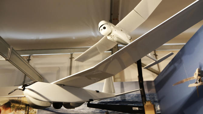 An AeroVironment Puma AE, front, and Raven small unmanned aircraft systems are displayed at the AeroVironment stand during Farnborough International Air Show, Farnborough, England, Tuesday, July 15, 2014. (AP Photo/Sang Tan)